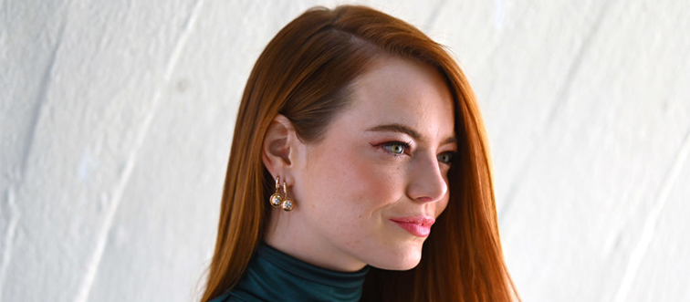 emma stone with her head turned wearing large earrings and a green turtleneck