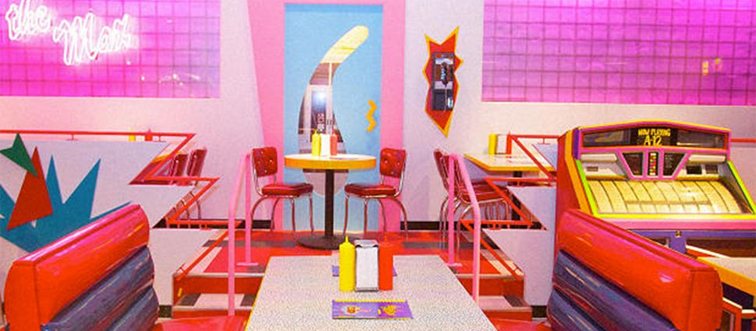 inside the max restaurant, featuring a booth, jukebox, and other tables with bright colors