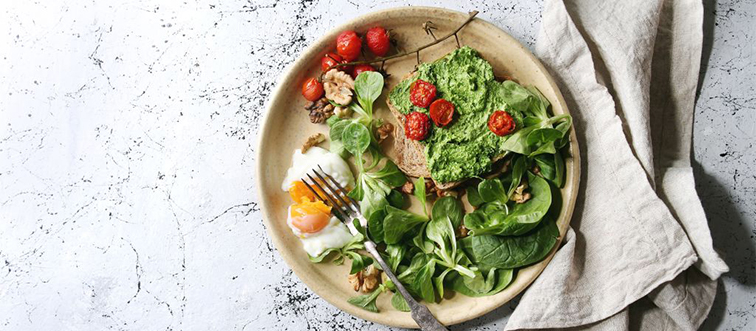a plate with greens, tomatoes, and an egg with a fork and napkin