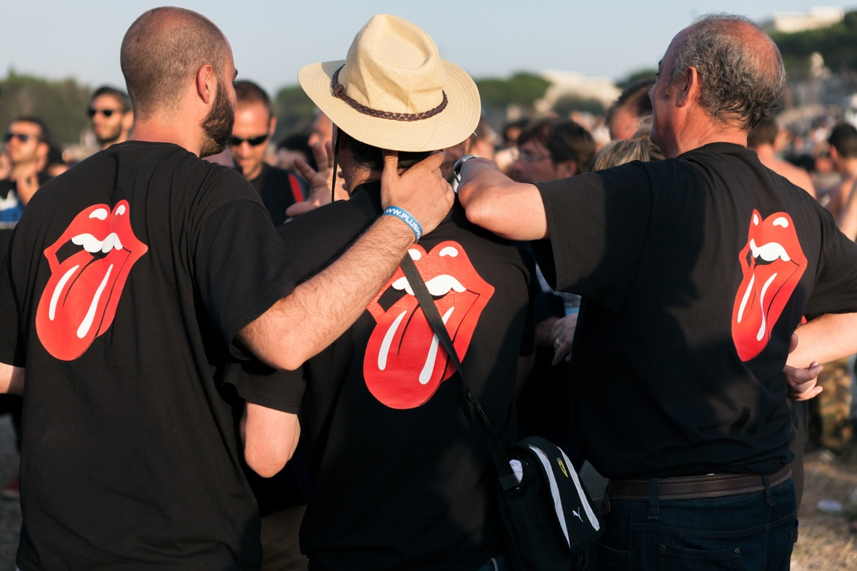 fans with the same t-shirts hugging each other waiting the show beginning at the Circus Maximus in Rome