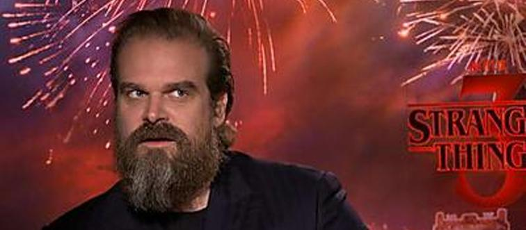 david harbour in front of a stranger things promotional background