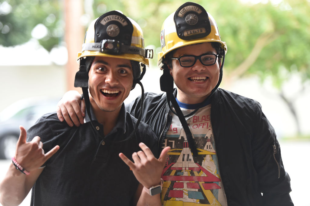 Two men are pictured wearing firefighter hats and smiling while one give the