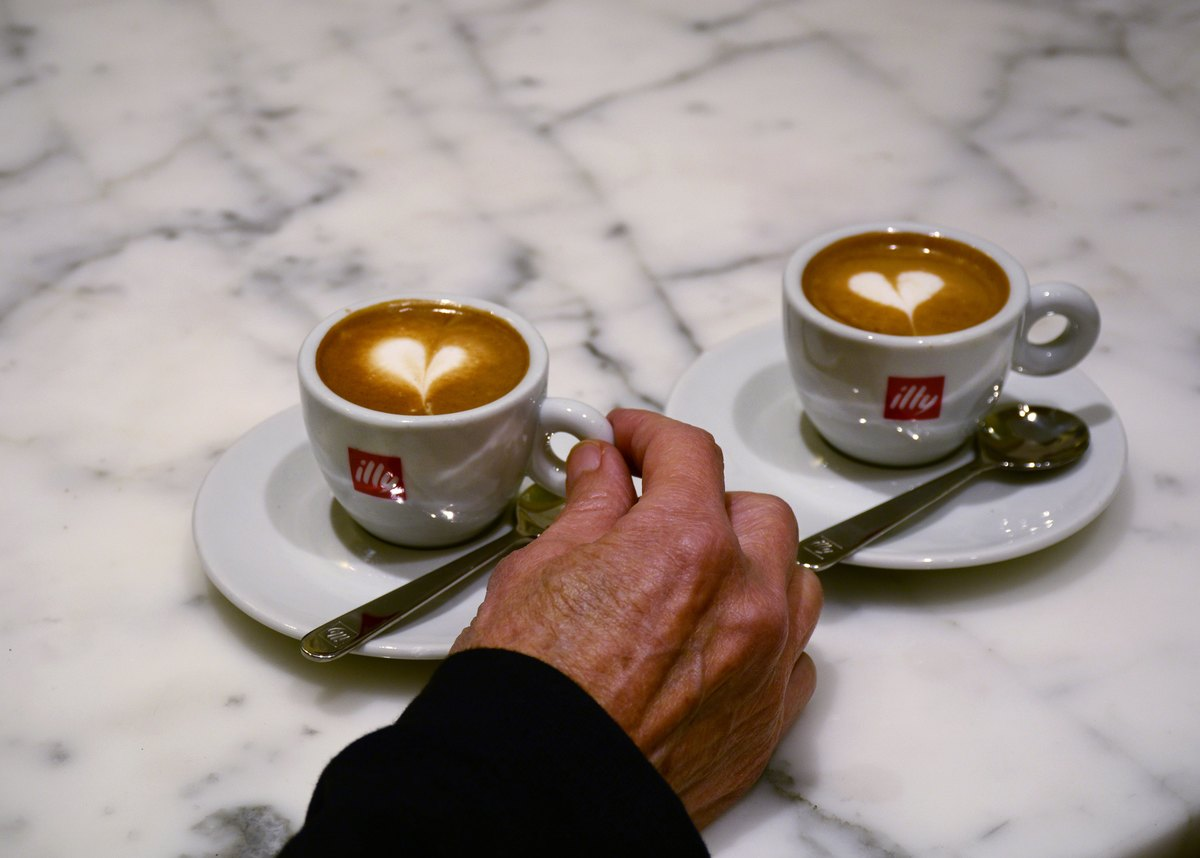 A couple enjoys cups of caffe' macchiato, sometimes called espresso macchiato, at a sidewalk cafe in Florence, Italy.
