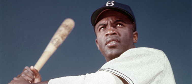 jackie robinson holding a bat in uniform