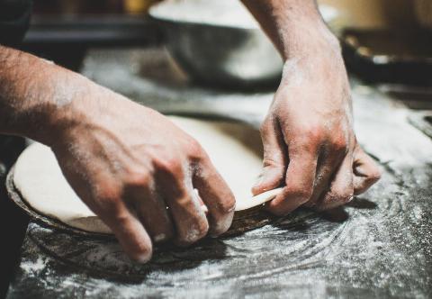 person molding pizza dough