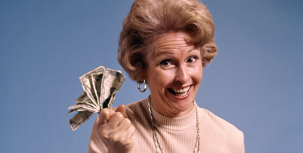 A woman holds up cash while wearing an enthused expression.