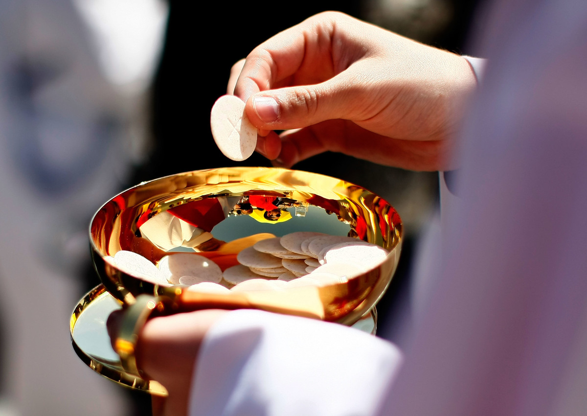 A priest holds a bowl of Holy Communion wafers.