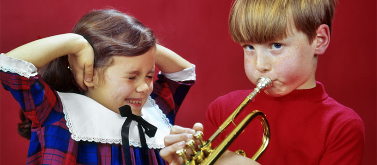 a boy playing a trumpet next to a little girl covering her ears