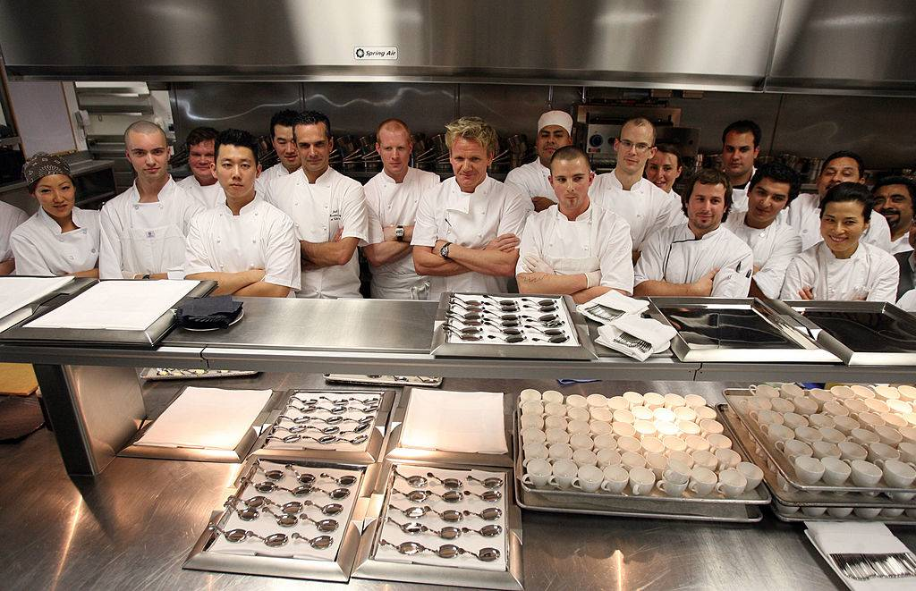 Chef Gordon Ramsay poses in the kitchen with his staff