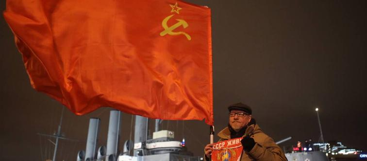 A man holds up a Soviet flag to commemorate the Bolshevik revolution.