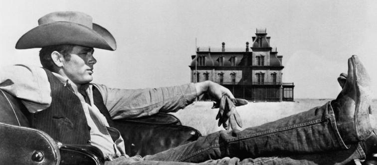 James Dean reclines in the back of a car wearing a cowboy hat.